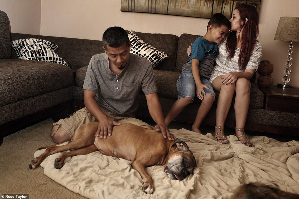 Vanessa Gangadyal consoles her son, eight-year-old Ian, while her husband, Michael Gangadyal, pets their dog, Ally, shortly after its passing.Founded by Dani McVety, the organization,Lap of Love, has been working with Caring Pathways to providea peaceful passing 'at home' euthanasia service